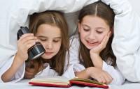 дети читают под одеялом с фонариком
