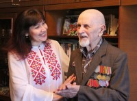 Сотрудник центра социального обслуживания населения Альбина Федорова поздравляет ветерана войны Александра Зюзина
