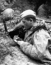 Западный фронт, 1941. Советский солдат в окопе пишет письмо.
